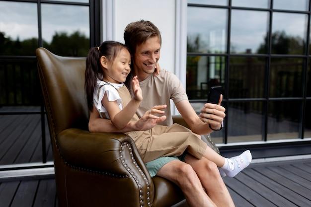 Córka przeprowadza wideorozmowę z mamą obok taty