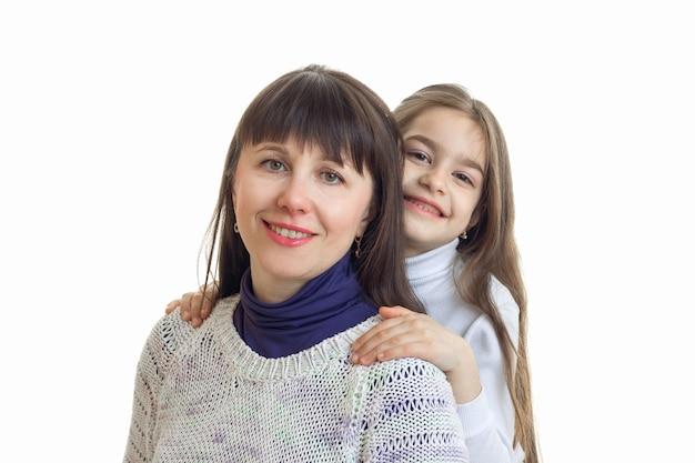 Córka przytula matkę i uśmiecha się do kamery na białym tle