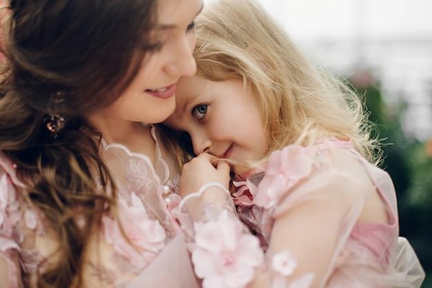 Córka przytula się do mamy i uśmiecha się.