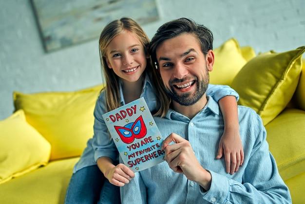 Córka przytula tatę i śmieje się na wakacjach. młody człowiek w domu ze swoją małą śliczną dziewczynką. szczęśliwego dnia ojca!