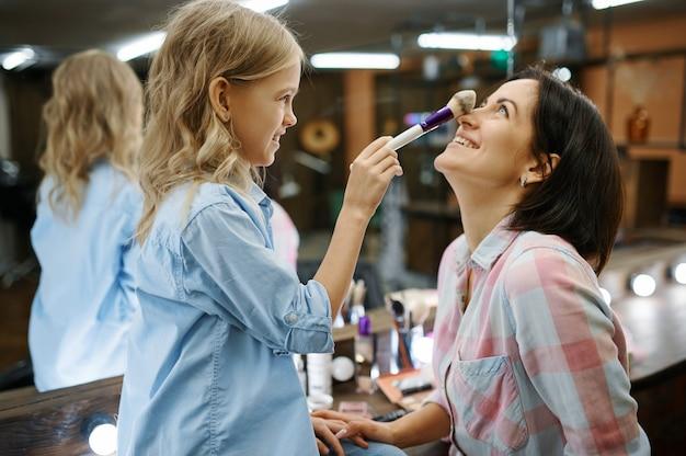 Córka robi makijaż matce w salonie