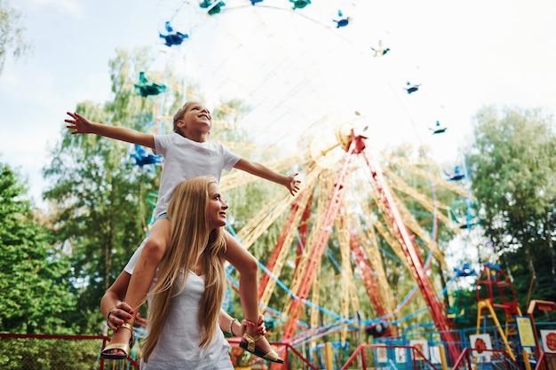 Córka siada na ramionach. wesoła dziewczynka jej mama dobrze się bawi w parku w pobliżu atrakcji.