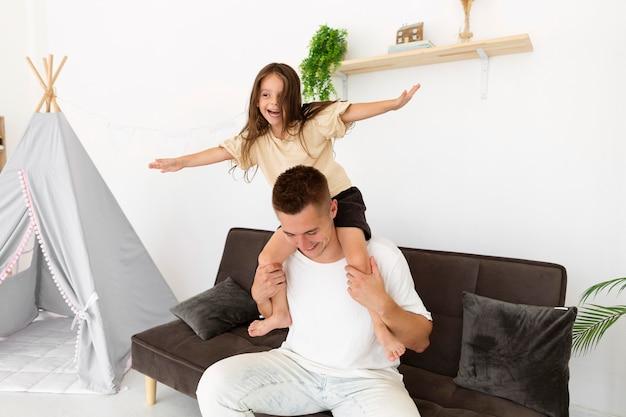Córka siedząca na ramionach ojca w domu