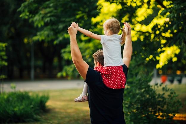 Córka siedzi na ramionach ojca