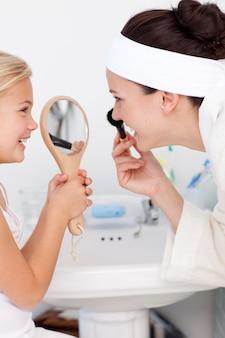 Córka trzyma lustro i macierzysty kładzenie makeup