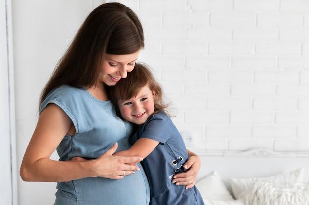Córka tuląca matkę w ciąży