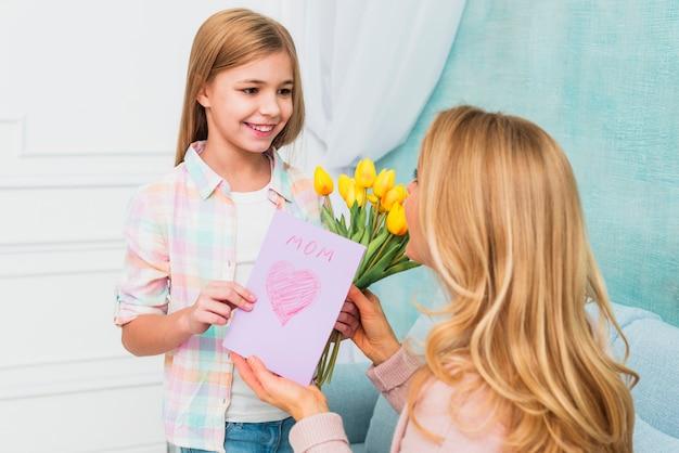 Córka uśmiecha się i przedstawia kwiaty i matki `s dzień pocztówka dla mamy