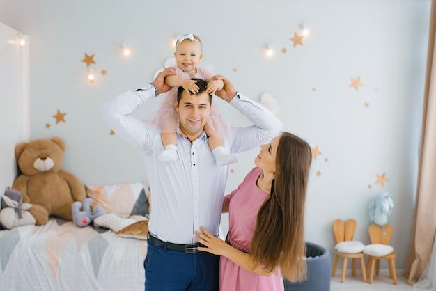 Córka uśmiecha się na ramionach ojca