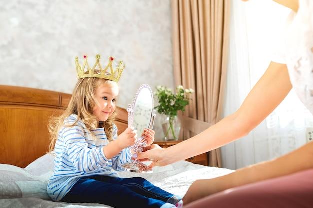 Córka w koronie bawi się z matką na łóżku