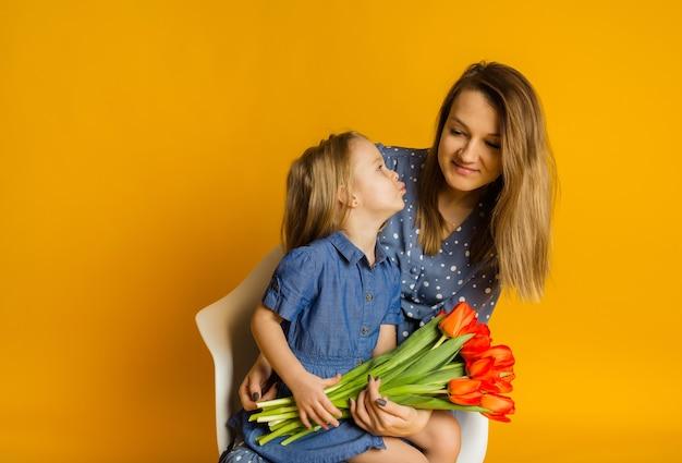 Córka w niebieskiej sukience z czerwonymi tulipanami całuje matkę na żółtej ścianie