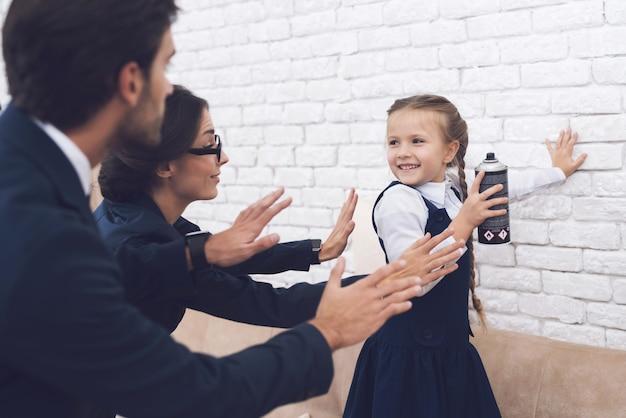 Córka w sukience stojącej na kanapie z sprayem.