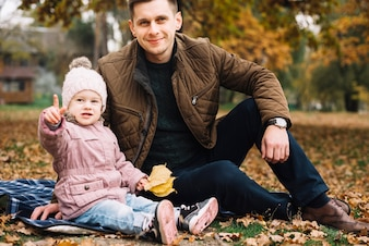 Córka wskazuje oddalony i obsiadanie z tata w jesień parku