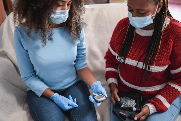 Córka wykonująca badanie glikemii na cukrzycę w okresie izolacji