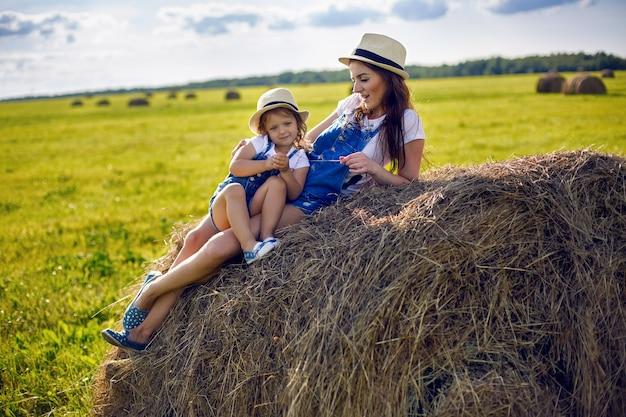 Córka z mamą stojącą na polu przy snopie w czapkach i dżinsowych kombinezonach podczas zachodu słońca