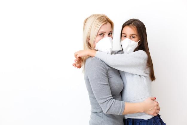 Córka z mamą w maskach chirurgicznych. rodzina z dziećmi w masce na twarz ffp1. ochrona przed wirusami i chorobami w zatłoczonych miejscach publicznych. sypialnia matki i córki nosić maskę ochronną, opieka zdrowotna