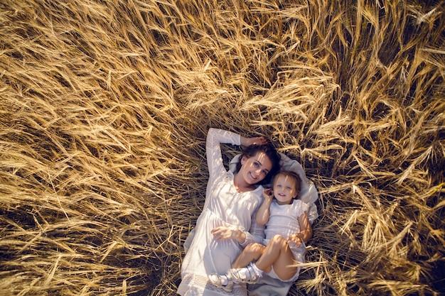 Córka z matką leży na ziemi na polu z uszami wieczorem latem