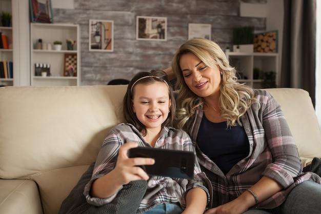 Córka z szelkami i jej matka oglądają wideo na smartfonie.