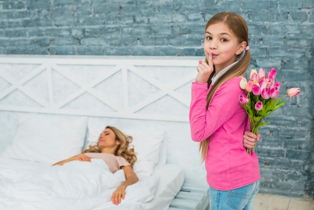 Córka z tulipanami trzyma palec na wargach