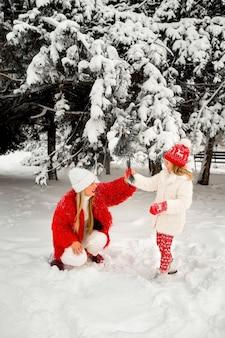 Córka zdmuchuje śnieg z gałęzi świerku na matkę. ferie.