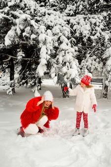 Córka zdmuchuje śnieg z gałęzi świerku na matkę. zimowa zabawa. mama i córka blondynka na śniegu