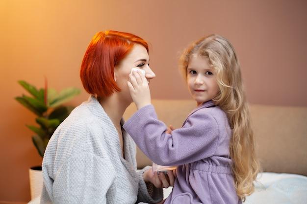 Córka zmusza mamę do makijażu w domu na łóżku