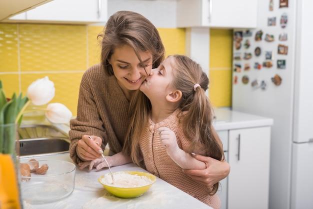 Córki całowania matka podczas gdy gotujący w kuchni