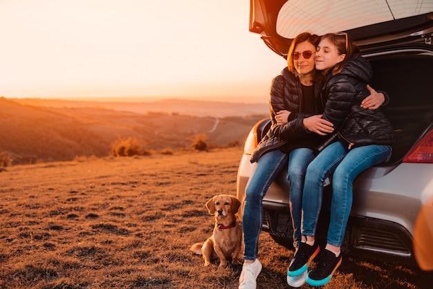 Córki obejmowania matka podczas gdy siedzący w bagażniku samochodu