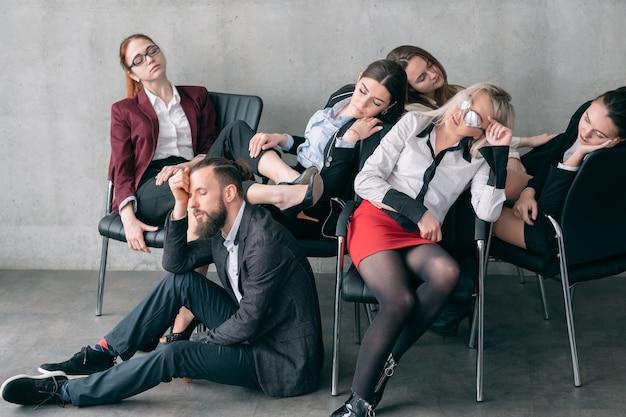 Coroczny audyt. przepracowane zmęczenie. zmęczeni menedżerowie śpiący na krzesłach i podłodze.