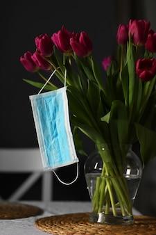 Coronavirus covid 19 koncepcja kwarantanny. bukiet wielkanocnych wiosennych kwiatów tulipanów z maską medyczną twarzy na stole w domu.