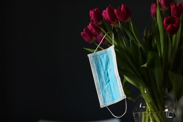 Coronavirus covid 19 koncepcja kwarantanny. wielkanocny wiosna tulipan kwitnie z twarzy medyczną maską na czerni