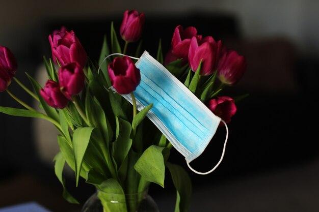 Coronavirus covid 19 koncepcja kwarantanny. wielkanocny wiosna tulipan kwitnie z twarzy medyczną maską na stole. kopia przestrzeń.