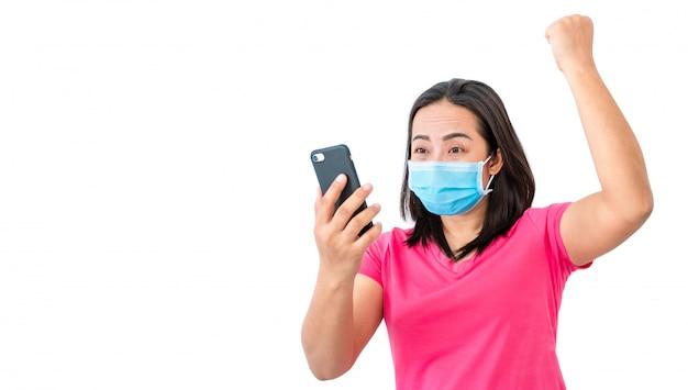 Coronavirus covid-19, podczas zatrzymania w domu zamaskowane kobiety używają telefonów do prowadzenia rozmów wideo z przyjaciółmi.