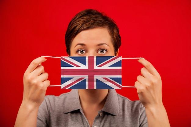 Coronavirus covid-19 w wielkiej brytanii. kobieta w medycznych maska ochronna z wizerunkiem flagi brytyjskiej.