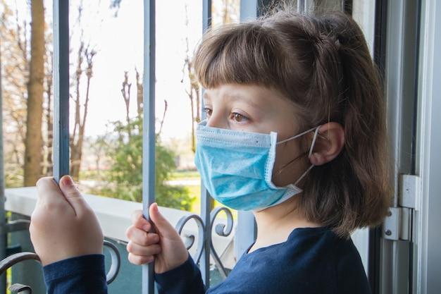 Coronavirus młoda dziewczyna w izolacji domowej auto kwarantanna w masce ochronnej na rozprzestrzenianie się wirusa choroby wyglądającego z okien