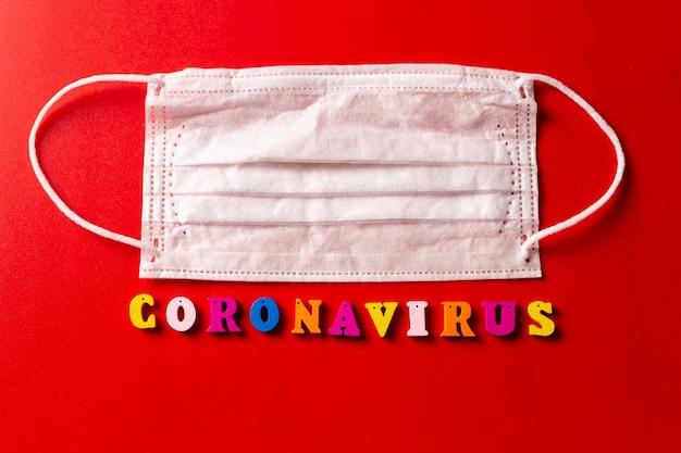 Coronavirus słowo wykonane z kolorowych liter na czerwonym tle. napis na koronarirusie medycznej maski ochronnej.