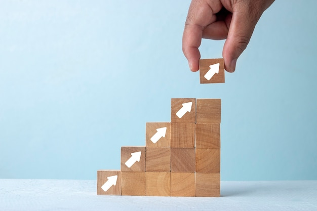 Corporate business growth concept, hand pick up wood block with white arrow