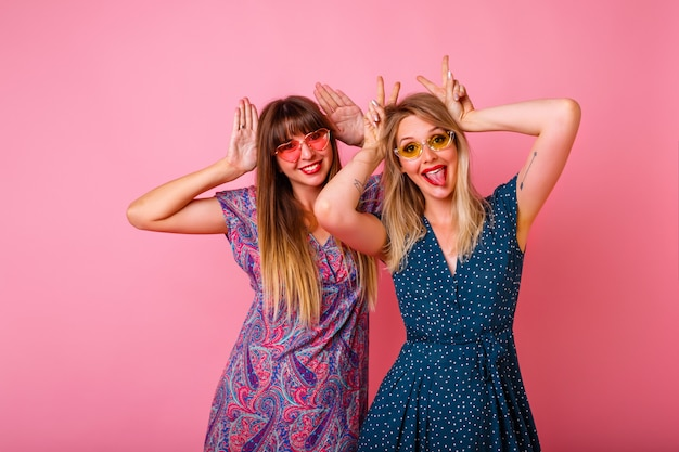 Coupe najlepszego przyjaciela, który dobrze się bawi, naśladując uszy królika rękami, ubrany w kolorowe letnie sukienki i okulary przeciwsłoneczne, różowa ściana, zabawa.