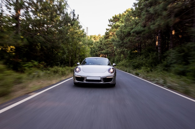Coupe w kolorze srebrnym z przednimi światłami na drodze.