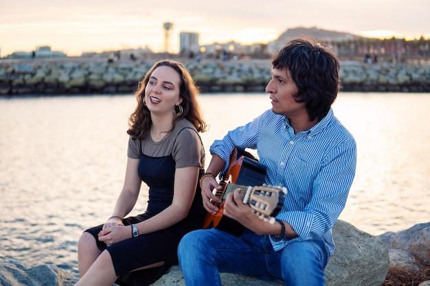 Coverband para muzyków gra na gitarze akustycznej i śpiewa w pobliżu plaży. morze na tle