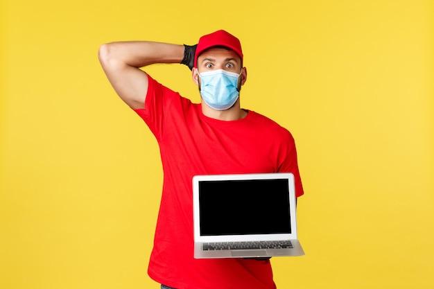 Covid-19, bezpieczne zakupy, ekspresowa dostawa i koncepcja śledzenia zamówień. zdezorientowany i zdenerwowany młody kurier popełnił błąd, patrząc zmartwiony, pokazując ekran laptopa, nosząc maskę medyczną