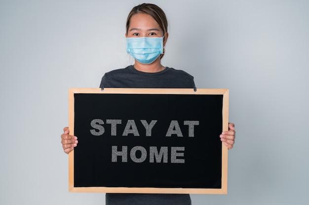 Covid-19 concept, azjatycka młoda kobieta ubrana w maskę ochronną na twarz z czarnym szerokim, pozostająca w domu trzymająca się za rękę, chroniąc przed koronawirusem lub epidemią covid-19.