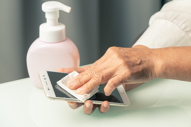 Covid-19 coronavirus koncepcja smartfona do czyszczenia rąk, starsze ręczne wycieranie smartfona żelem alkoholowym lub żelem antybakteryjnym do czyszczenia i usuwania wirusów, zarazków, bakterii