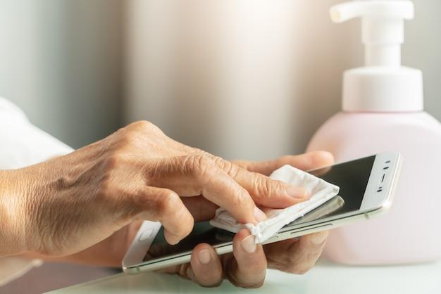 Covid-19 coronavirus koncepcja smartfona do czyszczenia rąk, starsze ręczne wycieranie smartfona żelem alkoholowym lub żelem antybakteryjnym do czyszczenia