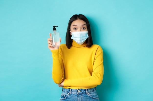 Covid-19, dystans społeczny i koncepcja pandemii. wesoła azjatka pokazująca środek dezynfekujący do rąk, zaleca stosowanie środka antyseptycznego od koronawirusa, noszenie maski medycznej.