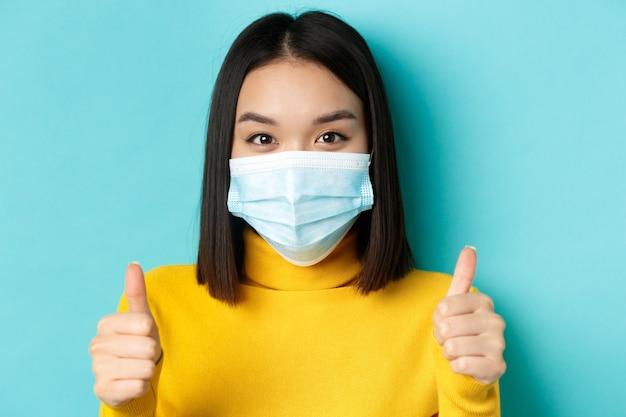 Covid-19, dystans społeczny i koncepcja pandemii. zamknij się młoda azjatycka kobieta w masce medycznej pokazując kciuki do góry, powiedz tak, chwal dobrą ofertę, stojąc na niebieskim tle.