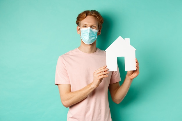 Covid-19 i koncepcja nieruchomości. młody szczęśliwy mężczyzna w masce na twarzy pokazujący wycinankę z papierowego domu i uśmiechnięty, oferuje nieruchomość na sprzedaż, stojąc na miętowym tle.