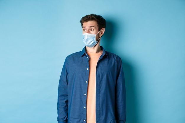 Covid-19 i koncepcja opieki zdrowotnej. zaskoczony kaukaski facet w masce, patrząc na bok na puste miejsce na baner, stojąc na niebieskim tle.
