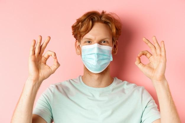 Covid-19 i koncepcja pandemii. przystojny facet z rozczochranymi rudymi włosami, ubrany w maskę medyczną na twarzy i pokazujący dobre znaki, stojący na różowym tle.