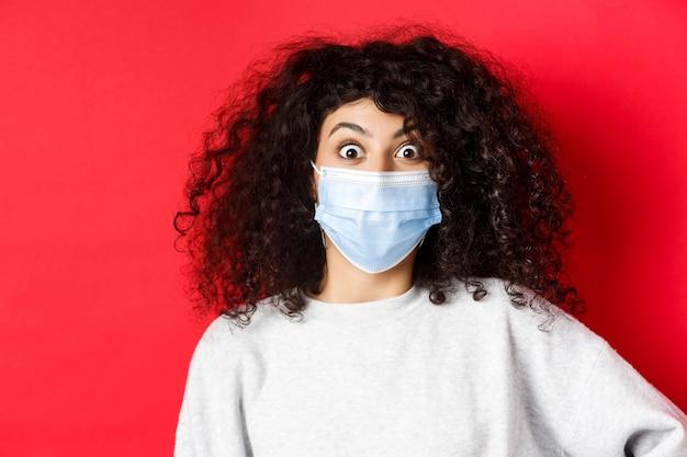 Covid-19 i koncepcja pandemii. zbliżenie zdziwionej kobiety w masce medycznej wyskakuje z oczu na coś niesamowitego, oglądającego promocję, stojącej na czerwonej ścianie.