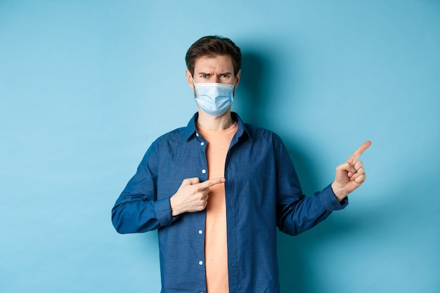 Covid-19 i koncepcja pandemii. zły mężczyzna w masce medycznej marszczący brwi, wskazujący palcami w prawy górny róg pustej przestrzeni, narzekający, stojący na niebieskim tle.